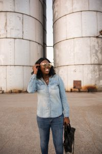 Tasha Robinson Imperfect Concepts wearing: Sunglasses: Quay X Desi, Shirt: Target, Jeans: American Eagle, Shoes: Charlotte Olympia and Bag: Balenciaga